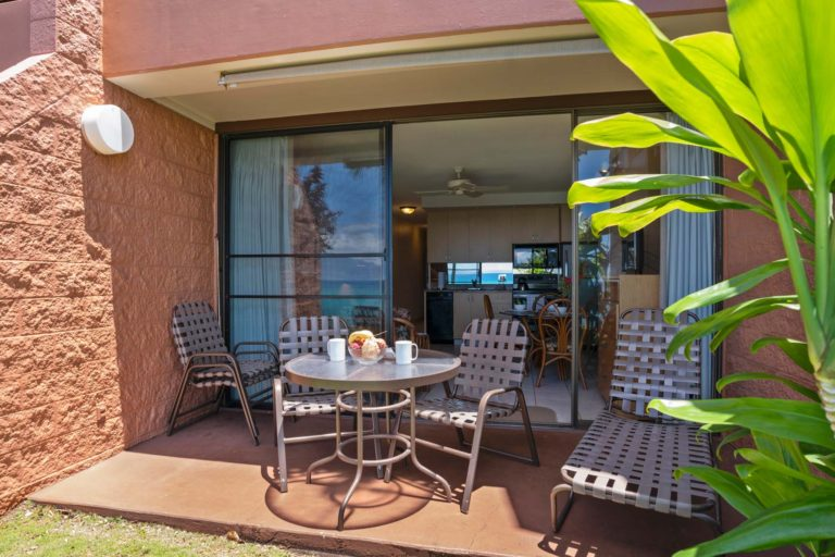 Photo of private patio with three chairs, table and lounging chair. Room 404