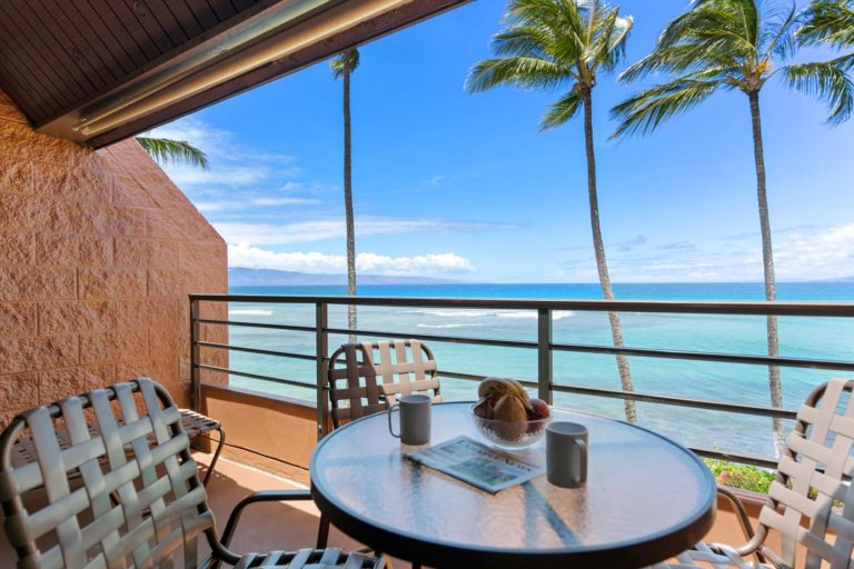 Photo of balcony with table, three chairs and ocean view. Unit 619