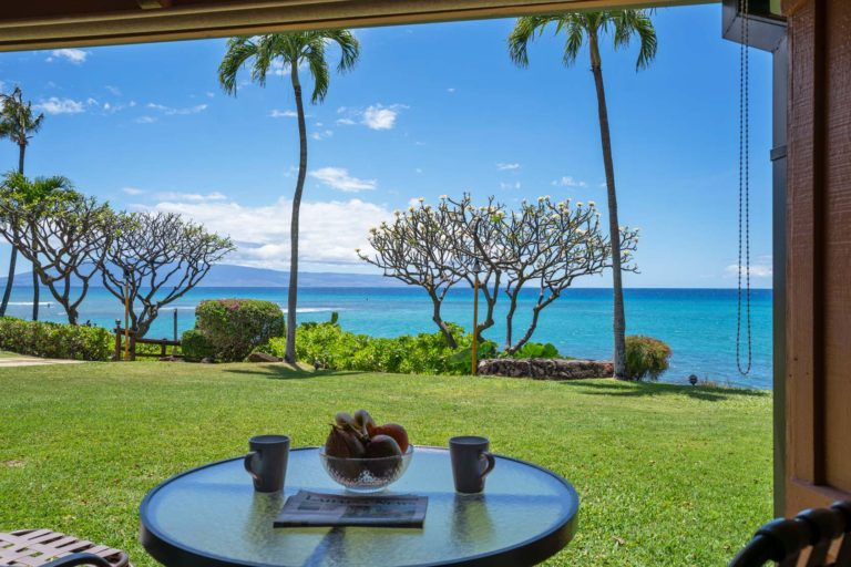 Photo of ground level private patio with ocean and Lanai Island view. Room 107