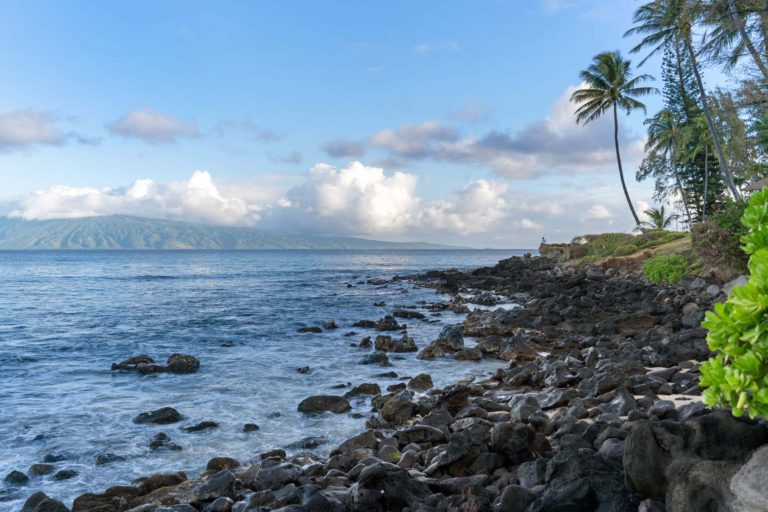 Photo of a rocky beach with the Molokai island in the background